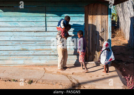 ANTANANARIVO, MADAGASCAR - JULY 3, 2011: Unidentified Madagascar father and his children in the street. People in Madagascar suffer of poverty due to  - Stock Photo