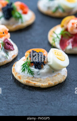 Selection of cocktail blinis with salmon, cured bresaola, crayfish, caviar, quail eggs and sour cream - gourmet party food. - Stock Photo