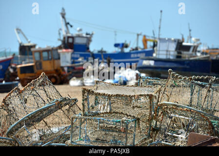 Fishing nets and trawlers on 'The Stade' - the shingle beach in Hastings Old Town, East Sussex, UK - Stock Photo