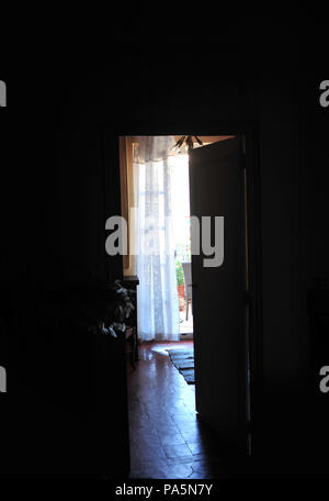 Early morning looking out of an open window and shutters leading to the outside balcony in a large French village house - Stock Photo