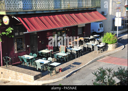 Looking from above down into the outside seating area of the local Sports Bar in Magalas, France early in the morning before people start to arrive - Stock Photo