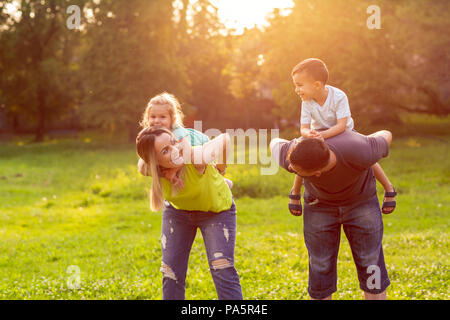 family, happiness, childhood and people concept - Happy parents giving piggyback ride to children - Stock Photo