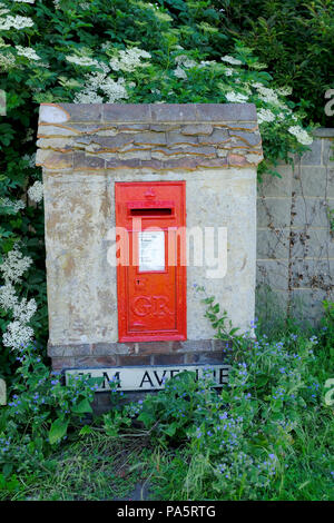 Wall recessed letter box surrounded by flowering plants - Stock Photo