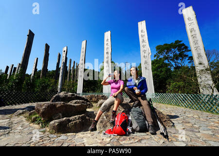 Hikers rest in front of wooden steles at Wisdom Path, Lantau Island, Hong Kong, China - Stock Photo