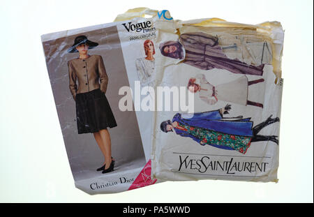 Vintage Christian Dior and Yves Saint Laurent sewing patterns on white background - Stock Photo