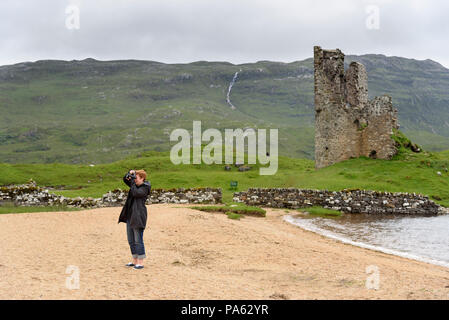 12-07-15, Highlands, Scotland, UK.  Tourist taking a photo in front of Ardvreck Castle.  Photo: © Simon Grosset - Stock Photo