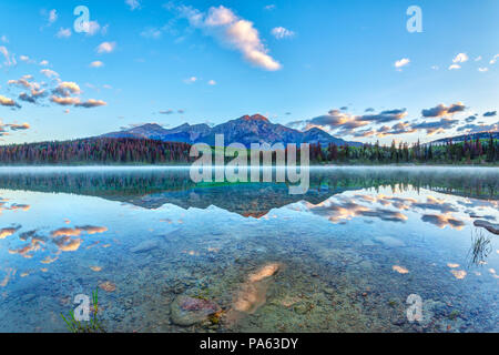 Sunrise over Patricia Lake in Jasper National Park with Pyramid Mountain in the background and misty fog on the water's surface. Calm waters create se - Stock Photo