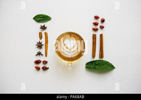 Delicious fresh morning cappuccino coffee in a mug on a white surface. Nearby are various ingredients - Stock Photo