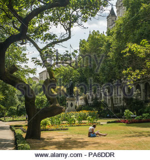 Lady sitting reading in Whitehall Gardens, London, England. Statue of English General Sir James Outram in the background. - Stock Photo