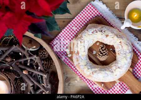 Christmas baked goods on a table and a flower with red leaves, candles. - Stock Photo