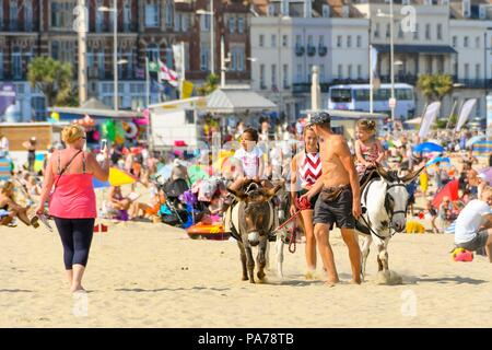 Weymouth, Dorset, UK.  21st July 2018. UK Weather.  Children enjoying a ride on a beach donkey at the seaside resort of Weymouth in Dorset on a hot sunny day on the first day of the school summer holidays.  Picture Credit: Graham Hunt/Alamy Live News - Stock Photo