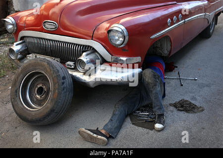 La Habana, La Habana, Cuba. 21st July, 2018. A mechanic repairs an old car made in the US in the last century on a street in Havana, Cuba.The Cuban Parliament holds a three days plenary session where is expected to discuss the draft of the new Constitution, which will recongnize the private property in the communist-run island. The new president Miguel DÃ-az-Canel, in office since april, is expected to announce his council of ministers. Credit: Ernesto Salazar/ZUMA Wire/Alamy Live News - Stock Photo