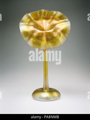 Vase. Culture: American. Designer: Designed by Louis Comfort Tiffany (American, New York 1848-1933 New York). Dimensions: 16 1/16 x 9 1/16 x 5 1/8 in. (40.8 x 23 x 13 cm). Maker: Tiffany Furnaces. Manufacturer: Attributed to Tiffany Glass and Decorating Company (American, 1892-1902) or. Date: ca. 1900-1915.  This so-called jack-in-the-pulpit vase is one of the quintessential shapes in Tiffany's oeuvre of blown glass. Essentially a flower form, it has a flattened globular base resembling a bulb rising into a slender stalk to an open blossom with a ruffled rim. The outer rim has a feathery appea - Stock Photo