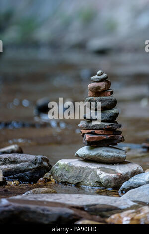 Balance and wellness concept. Close-up of river stones balanced in the shallow mountain creek. Low depth of field. Zen and spa inspired - Stock Photo