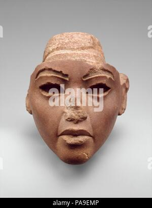 Face from a Composite Statue, probably Queen Tiye. Dimensions: H. 13.3 cm (5 1/4 in.); W. 12.5 cm (4 15/16 in.); D. 12.4 cm (4 7/8 in.)  H. of face 11 cm (4 5/16 in.). Dynasty: Dynasty 18. Reign: reign of Amenhotep III-Akhenaten. Date: ca. 1353-1336 B.C..  This quartzite head once belonged to a composite statue made of several different materials.  Based on the color of the stone (red being the conventional color for men), the owner was originally identified as Akhenaten.  However, the subject seems to have worn the standard tripartite wig, which frames the face with two thick hanks of hair wh - Stock Photo