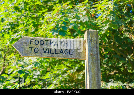 Old wooden signpost with Footpath to Village wriiten on it, in front of a green leafy background. - Stock Photo