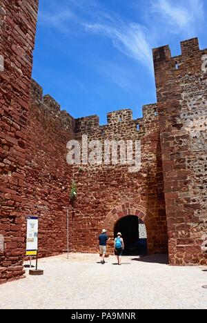 View of the Medieval castle entrance with a couple of tourists in the foreground, Silves, Portugal, Europe. - Stock Photo