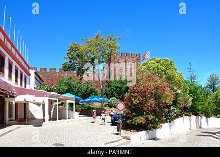 View of the Medieval castle with tourists walking along a city street in the foreground, Silves, Portugal, Europe. - Stock Photo