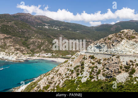 Stunning coastal road by a beautiful bay with turquoise water in Corsica in France near the Ile Rousse village. - Stock Photo