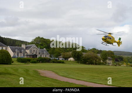 An air ambulance helicopter landing at Lawson Memorial Hospital in Golspie, Scottish Highlands - Stock Photo