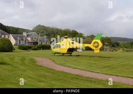 An air ambulance helicopter landed on the lawns outside the Lawson Memorial Hospital in Golspie, Scottish Highlands - Stock Photo