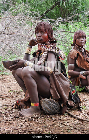 Two Hamer women with traditional dress  during Bull Jumping ceremony (Ukuli ritual) by Hamer Hamar tribe, Ethiopia - Stock Photo