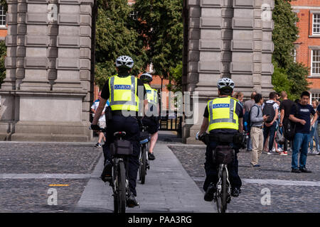Guards from Trinity College enter a common area on bicycles. - Stock Photo