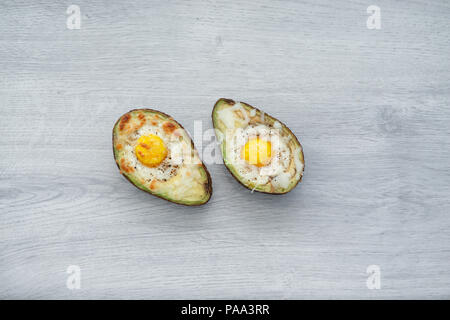 Two Eggs baked in avocado on plate - Stock Photo