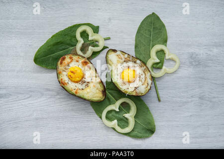 Two Eggs baked in avocado on wooden tabel and green leaves - Stock Photo