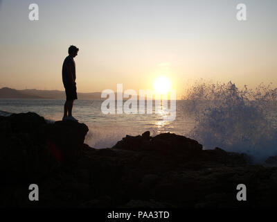 Silhouette of  man at sunset with waves crashing onto rocks - Stock Photo