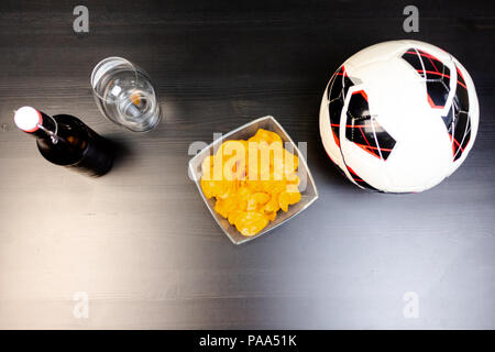 People prepared to watch football on TV with beer. There's beer on the table, ball, TV remote, snacks. Craft beer. Light background. The view from the - Stock Photo