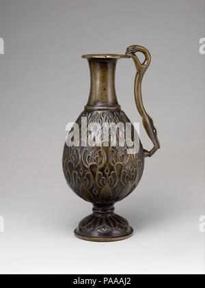 Ewer with a Feline-Shaped Handle. Dimensions: Max. H. 19 1/8 in. (48.5 cm); Max. Diam. 8 1/4 in. (21.1 cm). Date: 7th century.  This ewer demonstrates a continuation of Parthian and Sasanian forms during the early Islamic period in Iran. The lobed forms represent mountains and the vertical lines surmounted by budlike shapes are probably plants. Its overall composition and motifs demonstrate the transition from a figural style to a growing taste for rhythmic repeating patterns. The handle is shaped like an elongated cat peering at the heads of two birds depicted on the rim of the vessel, as tho - Stock Photo