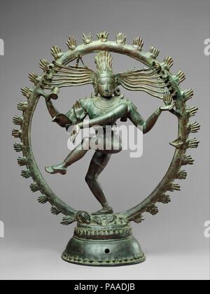 Shiva as Lord of Dance (Nataraja). Culture: Indian (Tamil Nadu). Dimensions: H. 26 7/8 in. (68.3 cm); Diam. 22 1/4 in. (56.5 cm). Date: ca. 11th century.  As a symbol, Shiva Nataraja is a brilliant invention. It combines in a single image Shiva's roles as creator, preserver, and destroyer of the universe and conveys the Indian conception of the never-ending cycle of time. Although it appeared in sculpture as early as the fifth century, its present, world-famous form evolved under the rule of the Cholas. Shiva's dance is set within a flaming halo. The god holds in his upper right hand the damar - Stock Photo