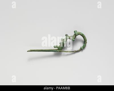 Bronze dragon-type fibula (safety pin). Culture: Villanovan. Dimensions: Other: 7 1/2 in. (19 cm). Date: 8th century B.C..  Dragon-type fibulae are a later variant of the serpentine type. Museum: Metropolitan Museum of Art, New York, USA. - Stock Photo