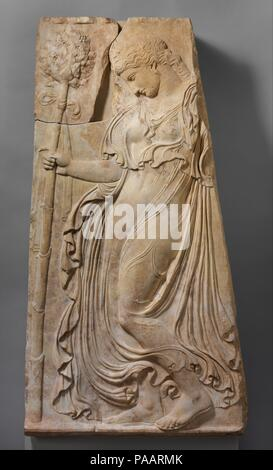 Marble relief with a dancing maenad. Culture: Roman. Dimensions: H. 56 5/16 in. (143 cm). Date: ca. 27 B.C.-A.D. 14.  Copy of a Greek relief of ca. 425-400 B.C. attributed to Kallimachos  Maenads were mythical women inspired by the god of wine, Dionysos, to abandon their homes and families and roam the mountains and forests, singing and dancing in a state of ecstatic frenzy. This figure, wearing an ivy wreath and carrying a thyrsos (fennel stalk) bedecked with ivy leaves and berries, moves forward, trancelike, her drapery swirling about her. She was copied from a famous relief of dancing maena - Stock Photo