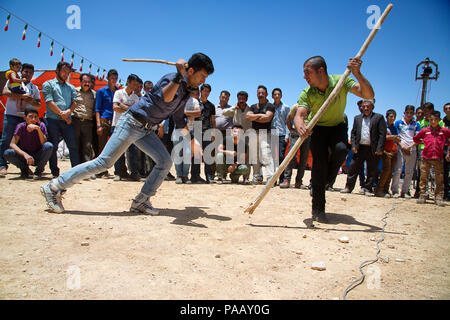 Young Qashqai men fighting with sticks during a traditional stick fight and wedding ceremony,  nomad people, Iran - Stock Photo