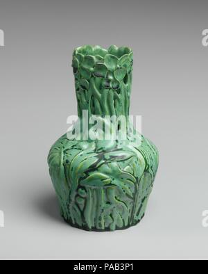 Vase. Culture: American. Dimensions: 7 3/4 in. (19.7 cm). Maker: Tiffany Studios (1902-32). Date: ca. 1904-09.  Louis Comfort Tiffany employed the motif of Queen Anne's lace, also known as 'wild carrot,' in his pottery, glass, and jewelry designs. Here, the bracts (stems on the underside of the blossoms) curl upward to form the organic shape of the vase. Queen Anne's lace was also the inspiration for the design of a cameo-cut glass vase (1997.409) and a hair ornament also in the Museum's collection (2001.249). Museum: Metropolitan Museum of Art, New York, USA. - Stock Photo