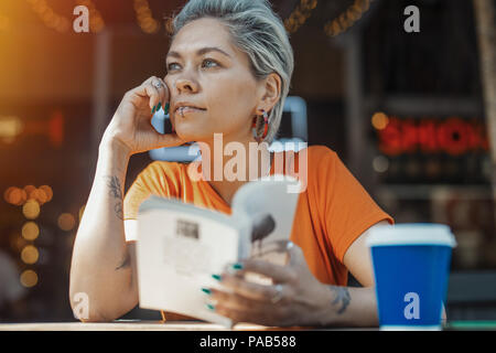 Attractive blonde girl holding book and drinking coffee at cafe - Stock Photo