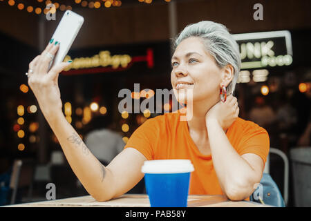 Attractive blonde girl making selfie at cafe - Stock Photo