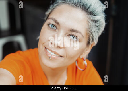 Attractive blonde girl in orange T-shirt making selfie at cafe - Stock Photo