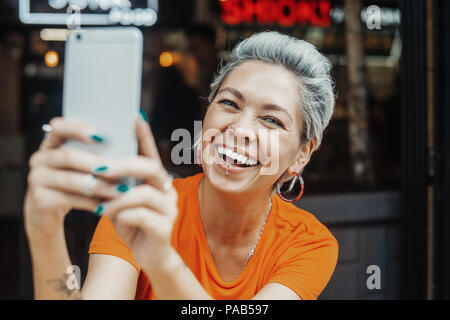 Attractive positive blonde woman in orange T-shirt making selfie at cafe - Stock Photo