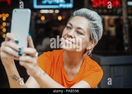 Close up of attractive blonde girl in orange T-shirt making selfie at cafe - Stock Photo