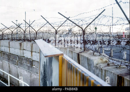1960s view of Berlin Wall, West Germany, looking into East Germany, GDR, through barbed wire with Czech hedgehog barriers. Digital conversion of slide taken in 1964 - Stock Photo