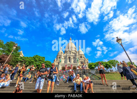 Paris, France - July 3, 2017: many people on the stairs of Basilica of Sacre Coeur de Montmartre in Paris in a sunny day with blue sky. Sacred Heart Church is a popular tourist landmark. Bottom view. - Stock Photo