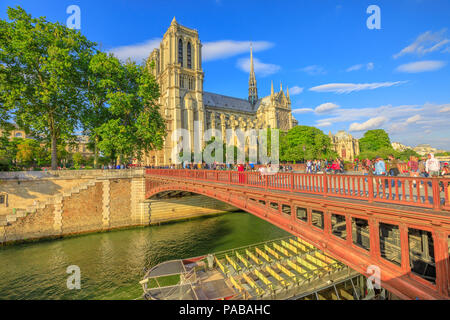 Paris, France - July 1, 2017: empty Bateaux-Mouches docked on the Seine under the red bridge with Notre Dame Cathedral on the Ile de la Cite in a sunny day and blue sky on background. - Stock Photo
