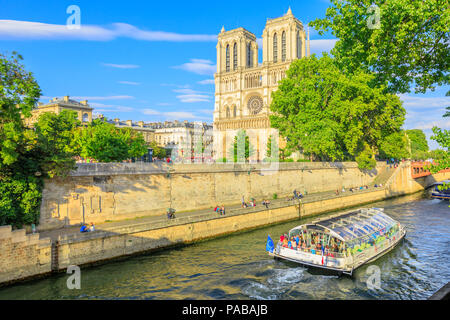 Paris, France - July 1, 2017: Bateaux-Mouches with many tourist during a trip at sunset on River Seine with Cathedral of Notre Dame on the Ile de la Cite on background. Sunny day, blue sky. - Stock Photo