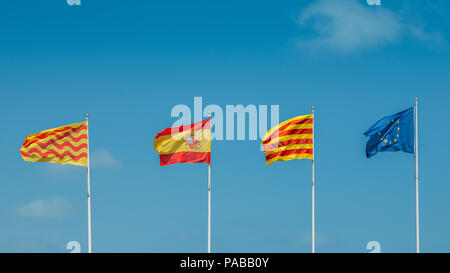 European Union, Catalonian, Spanish and Tarragonian flags flying on a mast against a blue sky. The regional Catalonian government wishes to separate f - Stock Photo