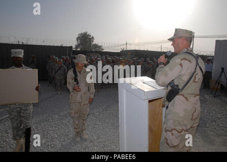 Capt. Kelly Schmader, commander of the 30th Naval Construction Regiment, delivers a message to service members during a memorial ceremony held at Kandahar Airfield. Sailors assigned to 30NCR and soldiers assigned to the 143D Expeditionary Sustainment Command, take time to honor those who lost their lives on Sept 11, 2001, and to pay tribute to the servicemen and women that have paid the ultimate sacrifice in support of Operations Iraqi Freedom and Enduring Freedom. 30NCR, homeported in Port Hueneme, Calif., and the 143d ESC, based in Orlando, Fla., are deployed to Afghanistan in support of Ope - Stock Photo