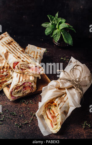Shawarma Sandwich - a fresh roll of thin lavash, filled with grilled meat, mushrooms, cheese and herbs. Oriental snack. On a metal background. - Stock Photo