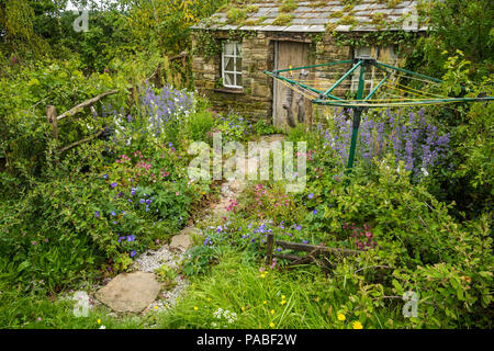 Beautiful show garden (natural planting, colourful borders, rustic cottage, airer) - Hay Time in The Dales, RHS Chatsworth Flower Show, England, UK. - Stock Photo